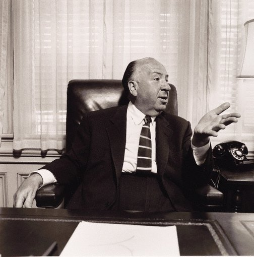 An image of Director, Alfred Hitchcock in his office at Universal Studios by Sid Avery